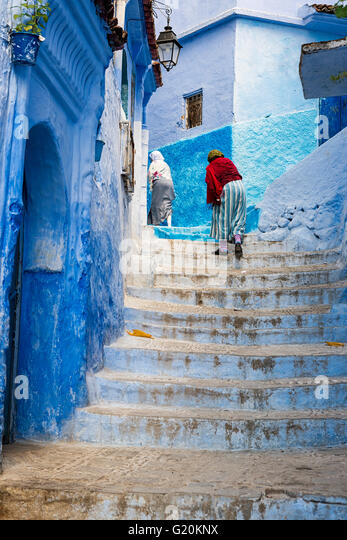 Chefchaouen, Morocco - April 10, 2016: Women climbing a stair in the town of Chefchaouen in Morocco. - Stock-Bilder