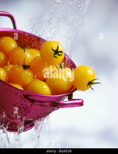 Yellow cherry tomatoes washing in colander with water - Stock Image