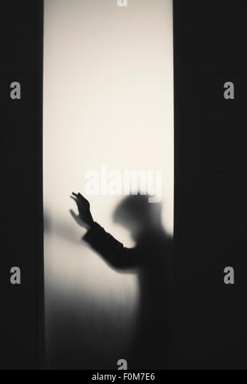 Silhouette of little child with raised arm. Conceptual image of childhood fears, abuse and safety of children. - Stock Image