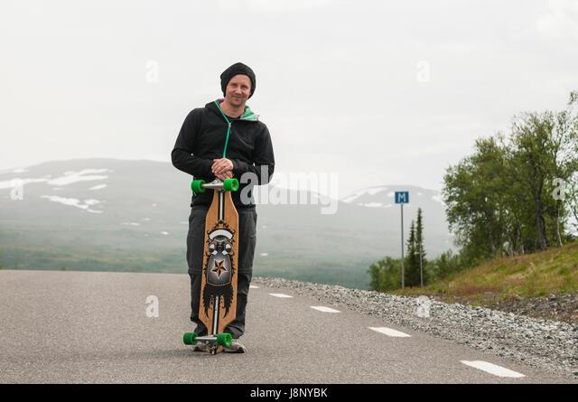 Man with skateboard, standing on road - Stock-Bilder