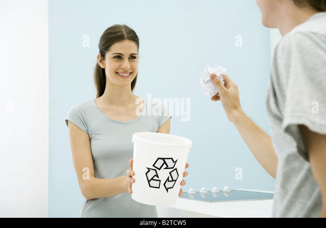 Man aiming paper ball toward recycling bin in woman's arms, cropped view - Stock Image