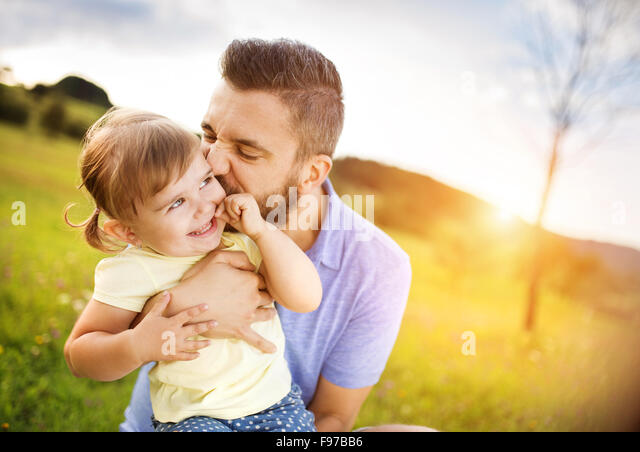 Hipster father playing with his little daughter in the green park. - Stock-Bilder