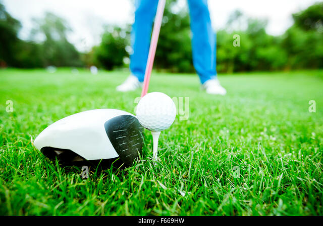 Golfer getting ready to take a shot. Wide angle photo and closeup - Stock Image