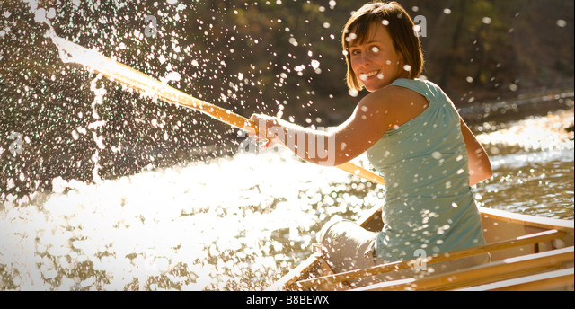 Woman splashing water behind canoe in the river - Stock Image