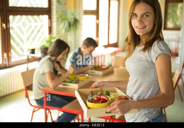 Student carrying lunch tray in school cafeteria - Stock Image
