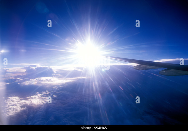 View of airplane wing and sky out of plane window - Stock Image
