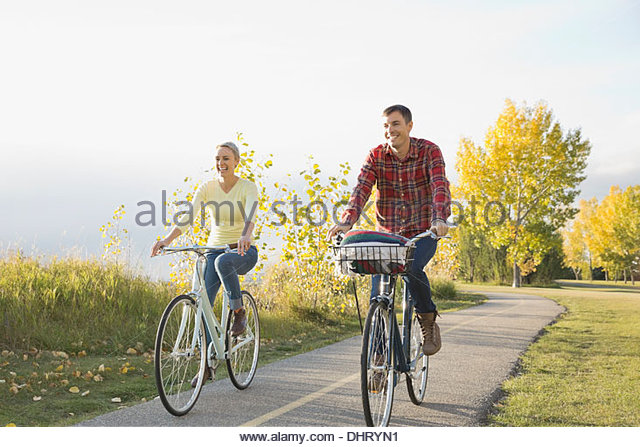Happy couple cycling on country road - Stock Image