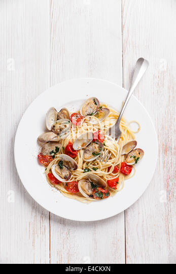 Seafood pasta with clams in tomato sauce Spaghetti Vongole on white wooden background - Stock Image