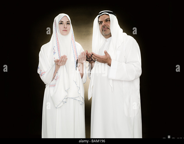 A man and woman holding prayer beads - Stock Image