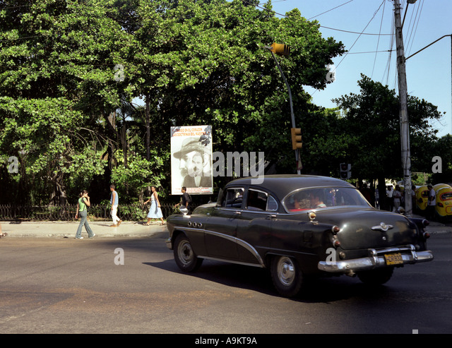 1950 s car driving past a poster of Fidel Castro in Havana Cuba - Stock Image