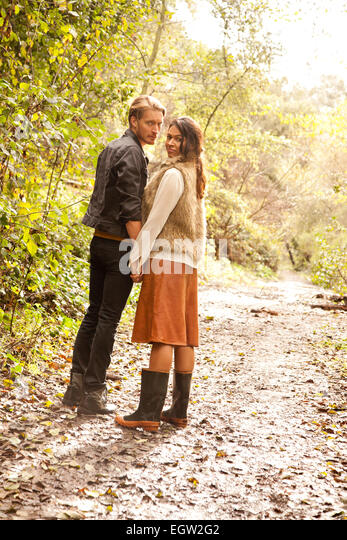 Woman and man on path in woods. - Stock Image