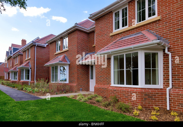 Photo of a row of brand new empty houses for sale on a housing development. - Stock-Bilder