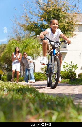A young African American family with boy child riding his bicycle and his happy excited parents giving encouragement - Stock-Bilder