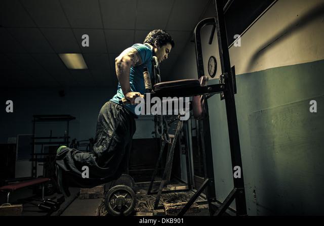 Weightlifter in dark gym, bench press - Stock Image