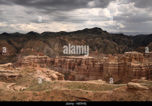 Single tourist on cliff top path of Charyn Canyon National Park Kazakhstan - Stock Image
