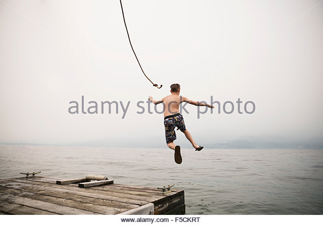 Boy jumping mid-air from dock into lake - Stock Image