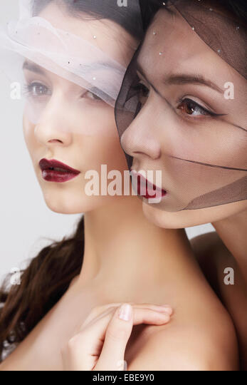 Fondness. Two Females in Veils Embracing - Stock Image