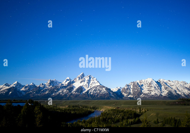 A full moon illuminates Grand Teton National Park with stars in the sky at the Snake River Overlook in Grand Teton - Stock Image