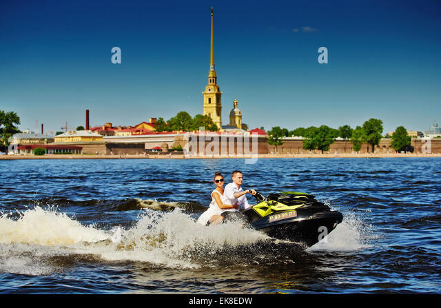 Newlyweds go on jet skis, the bride and groom on the background of Peter and Paul Fortress, the water area of the - Stock Image