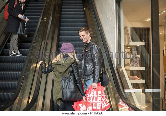 Young couple moving up escalator with shopping bags,  New York, USA - Stock Image