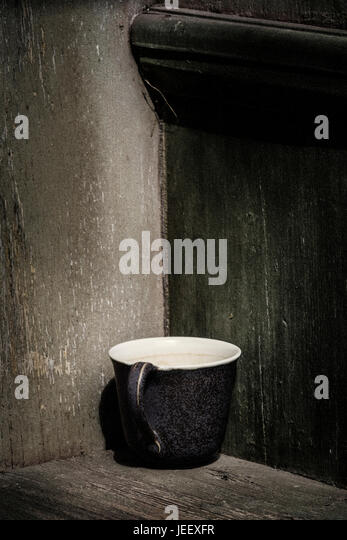 Old coffee cup in rustic setting. Vintage still life with empty mug and wooden background with copyspace. - Stock-Bilder