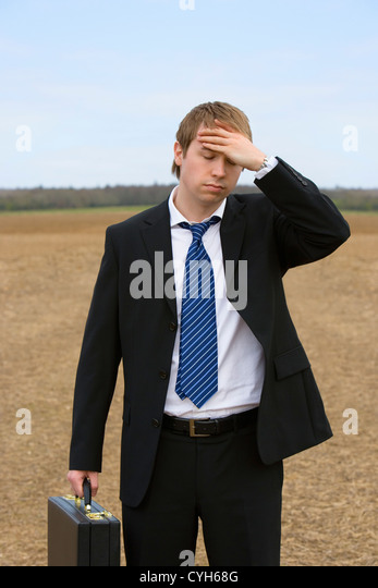 Young businessman with hand on forehead, standing in field - Stock Image