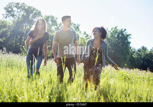Three people, a man and two women walking through tall grass in a meadow. - Stock Image