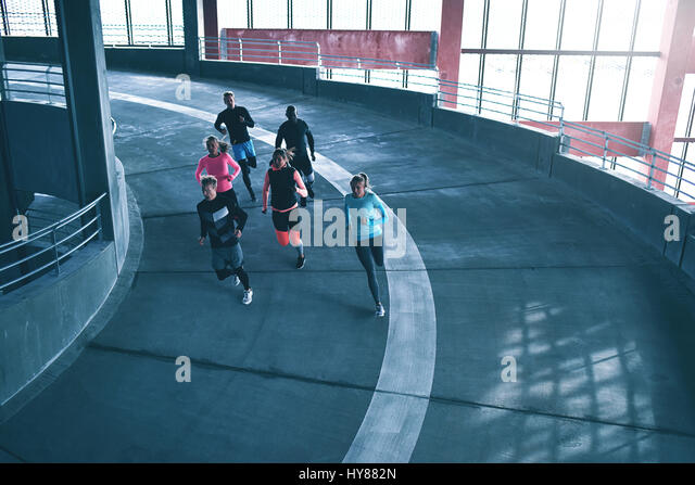 Group of young athletes training in gym and running on race track. - Stock Image
