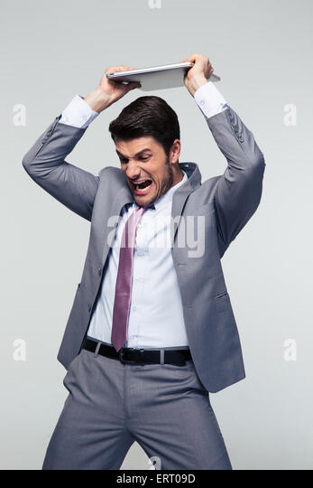 Angry businessman smashing his laptop over gray background - Stock Image