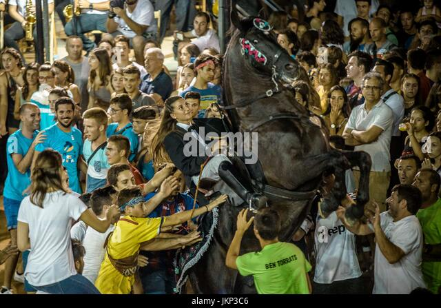 Es Castell, Spain. 24 July, 2017:  A 'caixer' (horse rider) rears up on his horse surrounded by a cheering - Stock Image