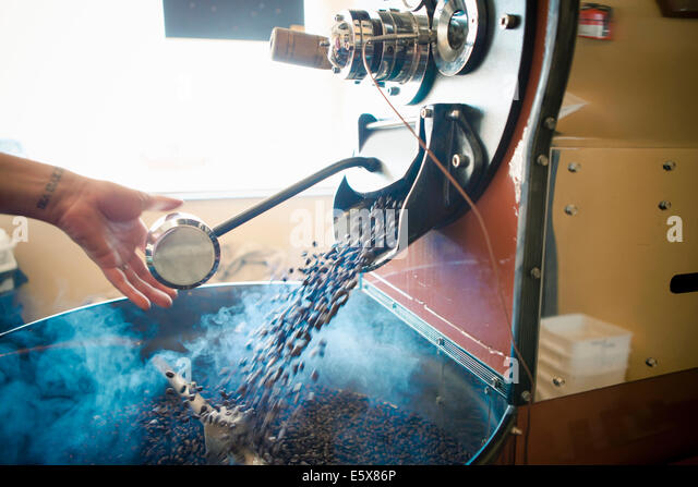 Female hand using industrial coffee roasting machine in cafe - Stock-Bilder
