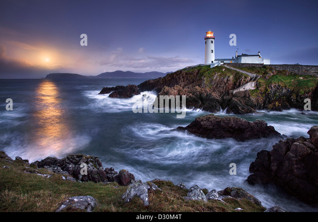 Fanad Head captured as a full moon rises behind the Lighthouse - Stock Image