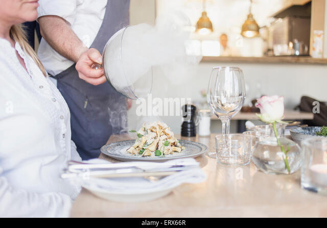 Steam coming out from food while waiter lifting lid in restaurant - Stock Image