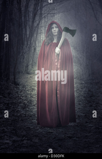 a woman in a red cloak with an axe - Stock-Bilder