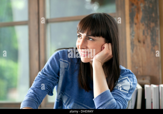 Portrait of brunette woman smiling with hand on chin - Stock-Bilder