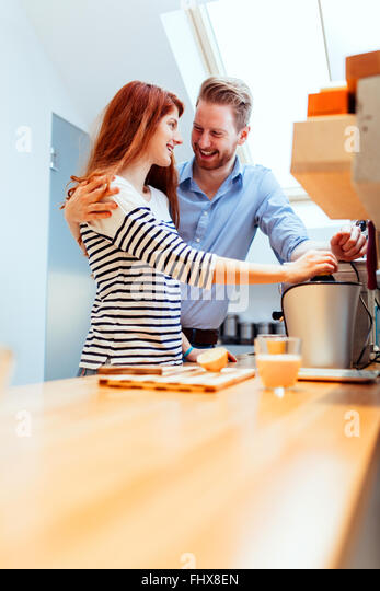 Attractive couple in kitchen preparing meals together - Stock Image