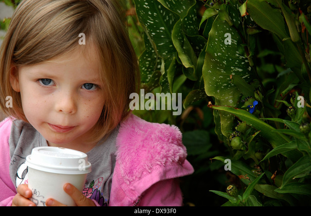 Little girl cools down her hot chocolate. - Stock Image