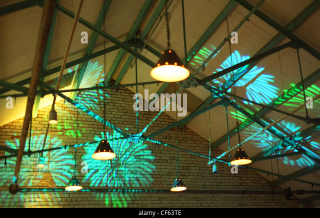 bright illumination. green and blue abstract shapes on brick wall - Stock Image