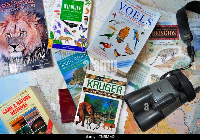 Binoculars, travel guides, guidebooks, African wildlife determination books and South African map for planning safari - Stock-Bilder