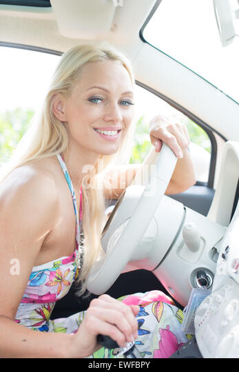 Portrait of happy woman sitting in car - Stock Image