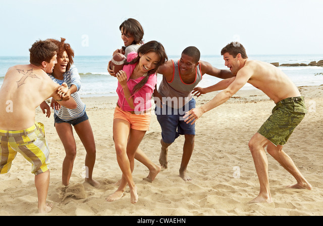 Friends on beach playing rugby - Stock Image