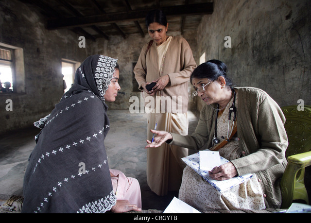 Volunteer Doctor (right) examines sick inhabitants of a village in India without any fee/royalty - Stock-Bilder