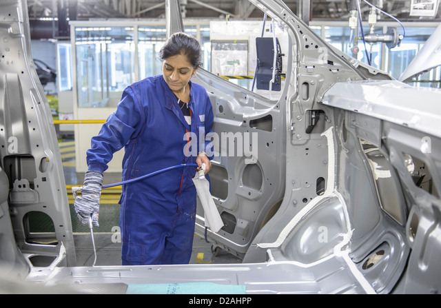 Worker applying sealant in car factory - Stock-Bilder