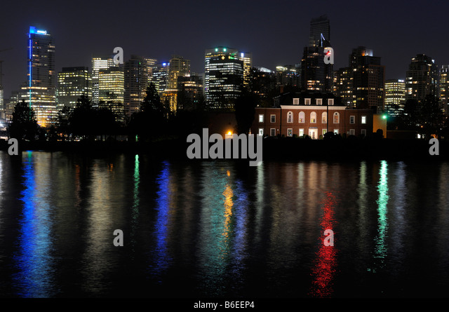 Vancouver skyline and Deadmans Island reflected in Coal Harbour from Stanley Park at night - Stock Image