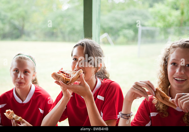 Girl soccer players eating pizza - Stock Image