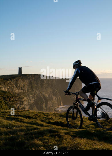 Cycling along the cliffs of Orkney - Stock Image