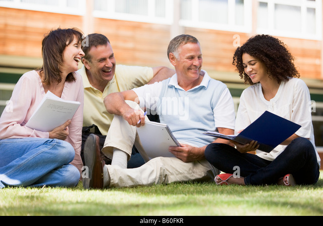 Adult students on lawn of school studying and talking - Stock Image