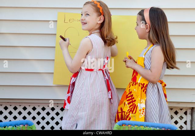 Girls making sign for selling homemade lemonade - Stock-Bilder