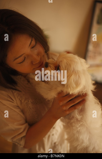 A woman playing with her dog - Stock Image