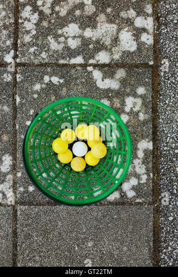 Directly above shot of golf balls in basket on paving stone - Stock-Bilder